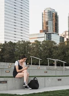 Junge frau, die das telefon im park betrachtet