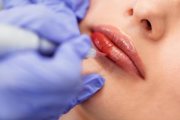 Junge frau, die dauerhaftes schminken auf den lippen im kosmetiksalon hat.