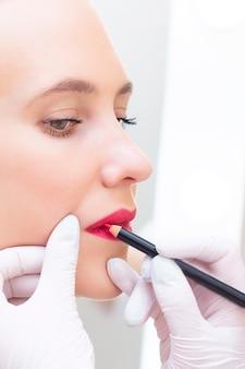 Junge frau, die dauerhaftes schminken auf ihren lippen im salon hat