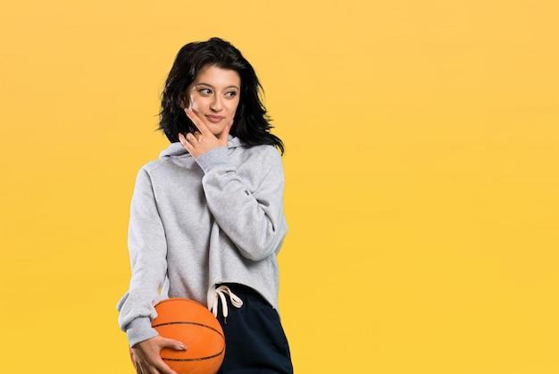 Junge frau, die den basketball denkt eine idee spielt