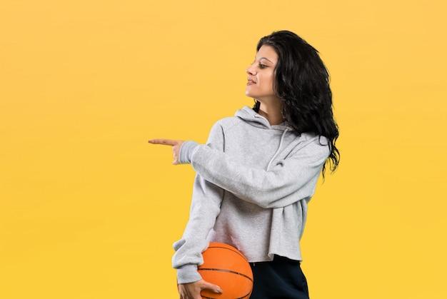 Junge frau, die den basketball zeigt auf die seite spielt, um ein produkt über lokalisiertem hintergrund darzustellen