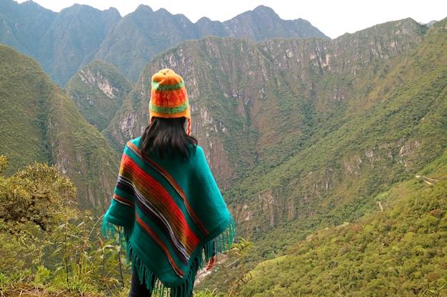 Junge frau, die den gebirgszug von berg huayna picchu, machu picchu, peru betrachtet