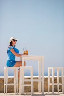 Junge frau, die den kalten kaffee genießt seeansicht trinkt. schönheit entspannen sich während der exotischen ferien auf dem strand, der frappe genießt