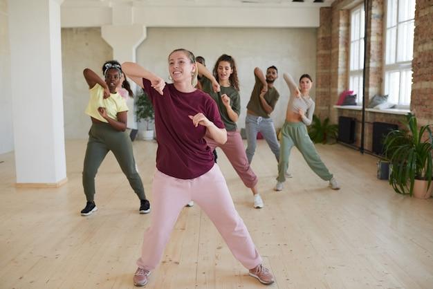 Junge frau, die den leuten tanzübungen während der klassen im fitnessstudio zeigt