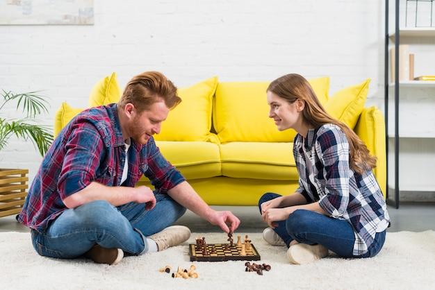 Junge frau, die den mann spielt das schachspiel im wohnzimmer betrachtet