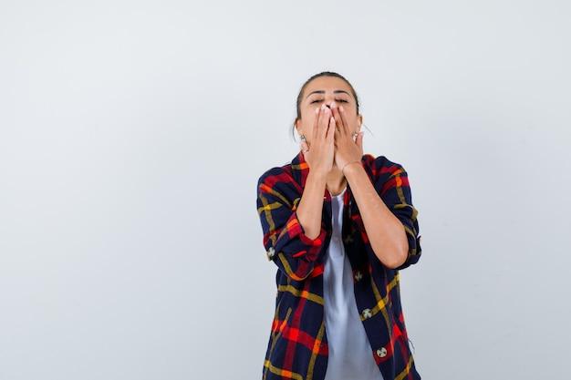 Junge frau, die den mund mit den händen im karierten hemd bedeckt und neugierig schaut, vorderansicht.