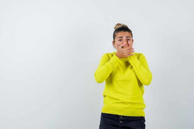Junge frau, die den mund mit den händen in einem gelben pullover und einer schwarzen hose bedeckt und aufgeregt aussieht