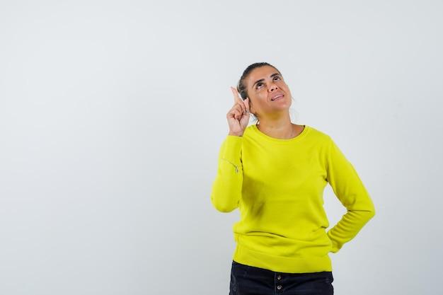 Junge frau, die den zeigefinger in der heureka-geste hebt, während sie die hand in gelbem pullover und schwarzer hose an der taille hält und vernünftig aussieht