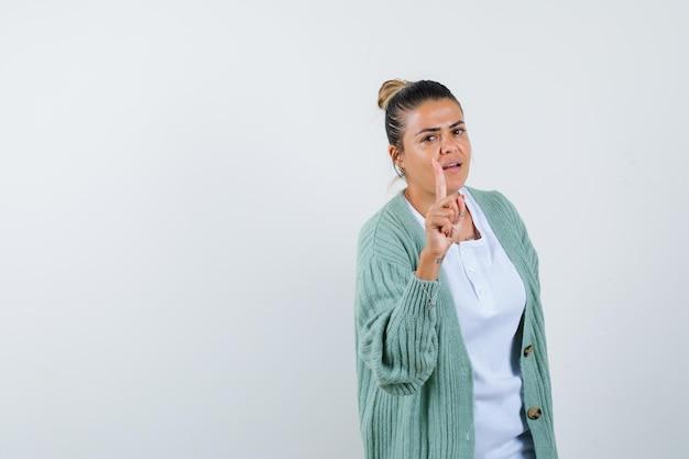 Junge frau, die den zeigefinger in der heureka-geste in weißem hemd und mintgrüner strickjacke hebt und vernünftig aussieht