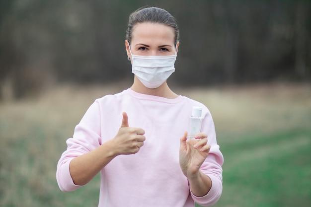 Junge frau, die desinfektionsmittel für desinfektionshände verwendet, zeigt daumen hoch, wie geste, mädchen in schutzmaske auf gesicht. desinfektion, desinfektion der hände gegen coronavirus, virusbakterien. pandemie covid-19