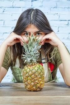 Junge frau, die die ananas betrachtet.