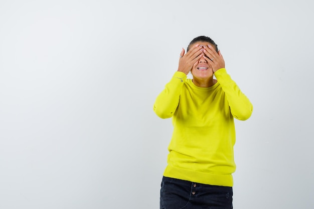 Junge frau, die die augen mit den händen in einem gelben pullover und einer schwarzen hose bedeckt und glücklich aussieht