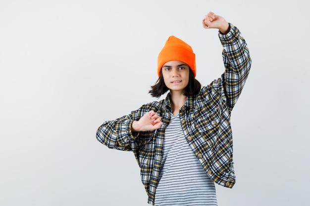 Junge frau, die die faust in einem orangefarbenen, karierten hemd mit hut hebt, das unsicher aussieht