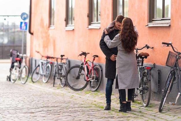 Junge frau, die die kleidung ihres mannes anpasst, während sie draußen auf einer ruhigen städtischen straße mit fahrrädern stehen, die gegen eine wand geparkt werden