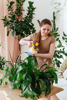 Junge frau, die die pflanzen mit vertikalem wasserrahmen besprüht