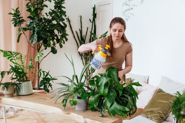 Junge frau, die die pflanzen mit wasserhorisontalrahmen besprüht
