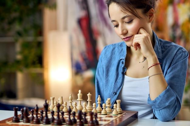Junge frau, die die schachfiguren auf dem brett betrachtet und über einen zug nachdenkt, während sie schach spielt