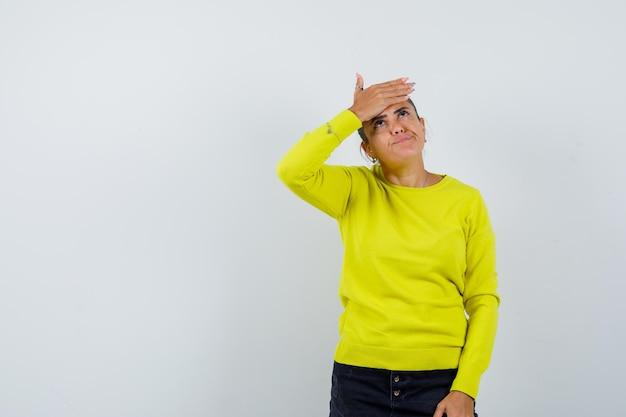 Junge frau, die die stirn bedeckt, in gelbem pullover und schwarzer hose nach oben schaut und nachdenklich aussieht looking
