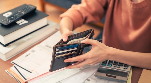 Junge frau, die die taschengeldbörse hält und mit geld, kreditkarte und spesenrechnung und berechnung über schuldenrechnungen monatlich am tisch im haus öffnet.
