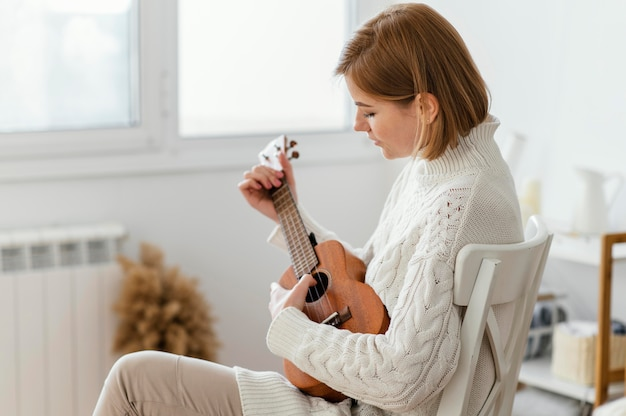 Junge frau, die die ukulele spielt