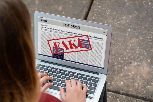 Junge frau, die digitale gefälschte nachrichten auf laptop liest