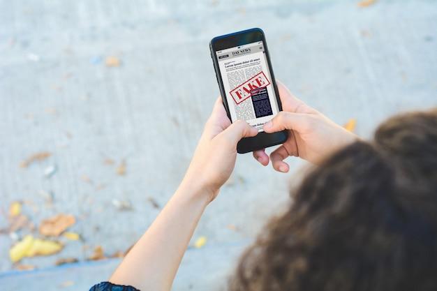 Junge frau, die digitale gefälschte nachrichten auf smartphone liest