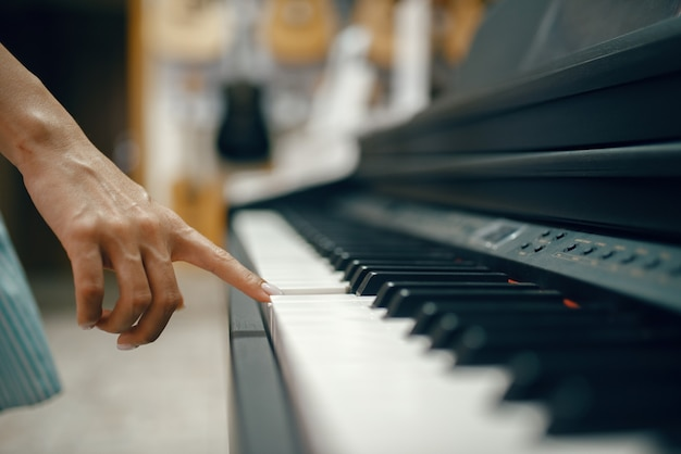 Junge frau, die digitales klavier im musikgeschäft wählt