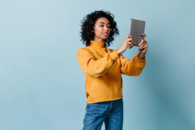 Junge frau, die digitales tablett hält