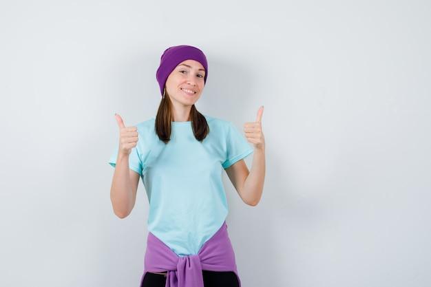 Junge frau, die doppelte daumen hoch in blauem t-shirt, lila mütze zeigt und fröhlich aussieht. vorderansicht.
