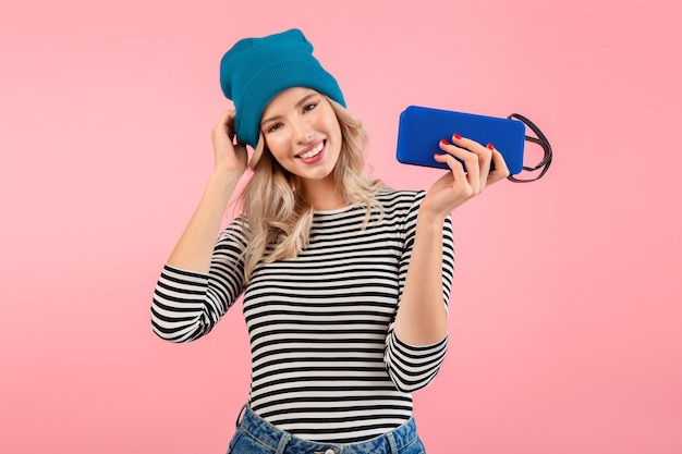 Junge frau, die drahtlosen lautsprecher hält, der musik trägt, die gestreiftes hemd und blauen hut lächelnd auf rosa posierend trägt