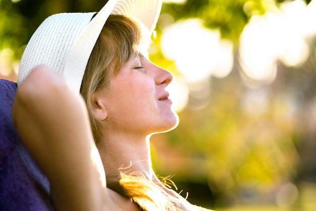 Junge frau, die draußen am sonnigen sommertag entspannt. glückliche dame, die auf bequemem strandkorb liegt und tagträumen denkt. ruhiges schönes lächelndes mädchen, das frische luft genießt, die mit geschlossenen augen entspannt.