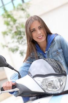 Junge frau, die draußen auf motorrad sitzt