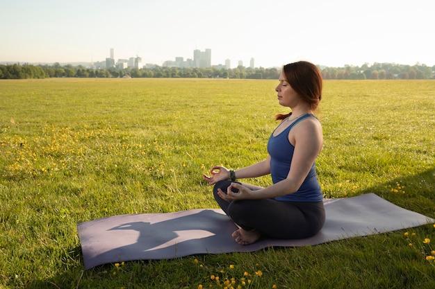 Junge frau, die draußen auf yogamatte meditiert