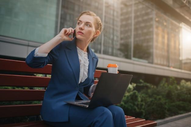 Junge frau, die draußen sitzt und laptop verwendet. geschäftsfrau arbeitet. tasse kaffee halten. und gleichzeitig telefonieren