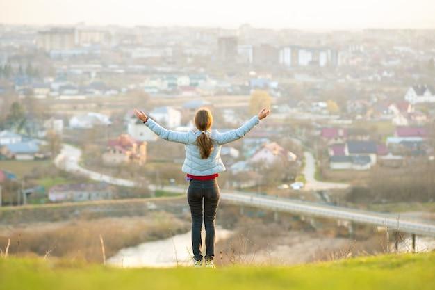 Junge frau, die draußen steht und ihre hände erhöht, die stadtansicht genießen. entspannungs-, freiheits- und wellnesskonzept.