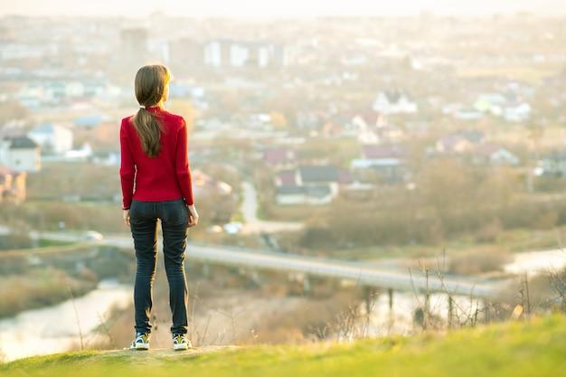 Junge frau, die draußen steht und stadtblick genießt. entspannungs-, freiheits- und wellnesskonzept.
