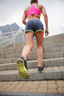 Junge frau, die draußen trainiert. es ist nicht einfach, die stufen hinaufzulaufen
