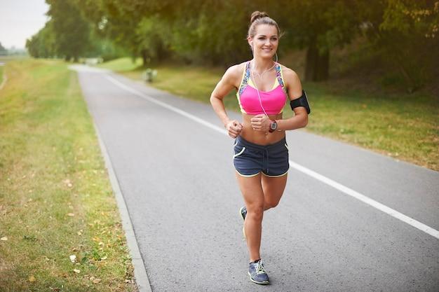 Junge frau, die draußen trainiert. joggen ist meine morgenroutine