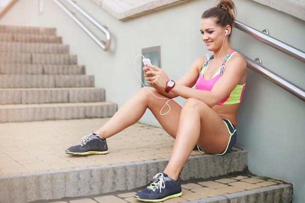 Junge frau, die draußen trainiert. kurze sms und ich bin zurück zum joggen