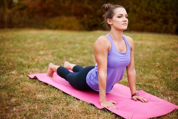 Junge frau, die draußen yoga macht. diese art von übungen kann ihnen geduld beibringen