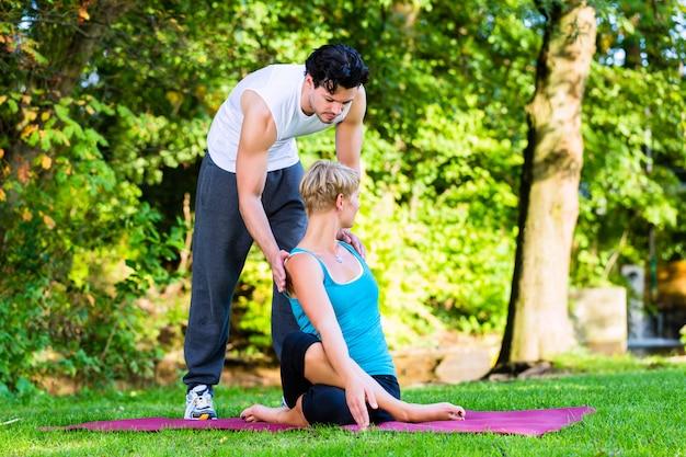 Junge frau, die draußen yoga mit trainer tut