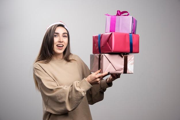Junge frau, die drei kisten der weihnachtsgeschenke hält.