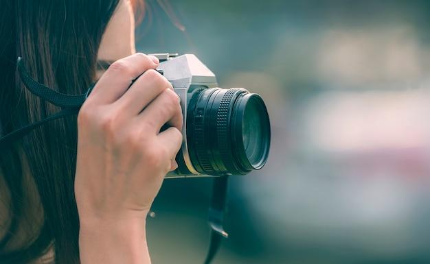 Junge frau, die dslr camara hält und fotos im freien macht Premium Fotos