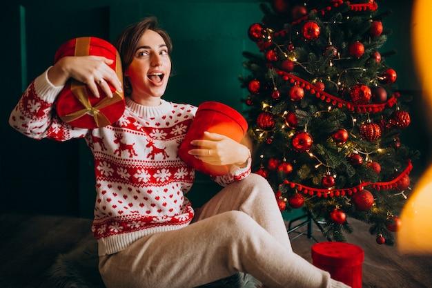 Junge frau, die durch den weihnachtsbaum mit roten kästen sitzt