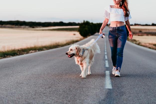 Junge frau, die durch die straße mit ihrem golden retriever-hund bei sonnenuntergang geht. haustiere im freien