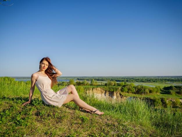 Junge frau, die durch eine klippe draußen auf natur sitzt. attraktives mädchen mit einem weißen kleid, das im freien aufwirft. weibliches modell, das in einem feld einen sonnigen sommertag aufwirft.
