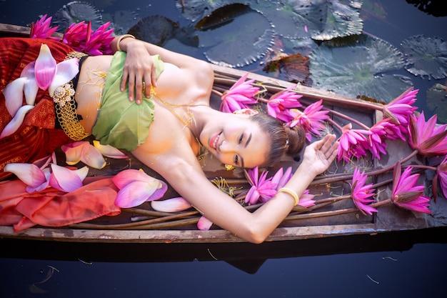 Junge frau, die durch rosa lotus on boat in lake liegt