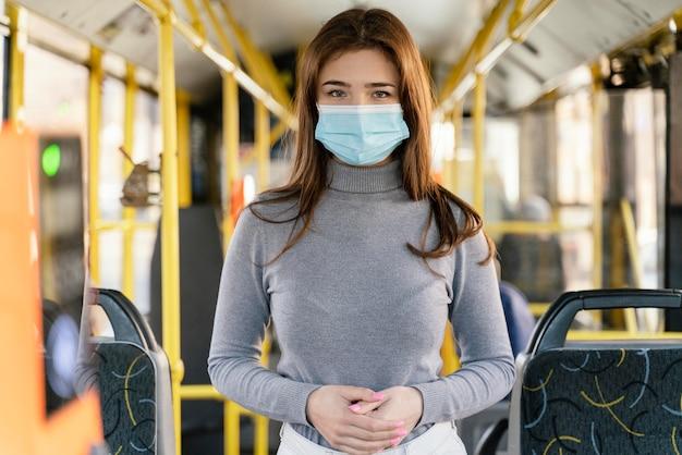 Junge frau, die durch stadtbus mit chirurgischer maske reist