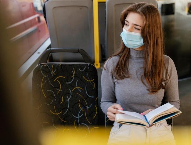 Junge frau, die durch stadtbus reist, der ein buch liest