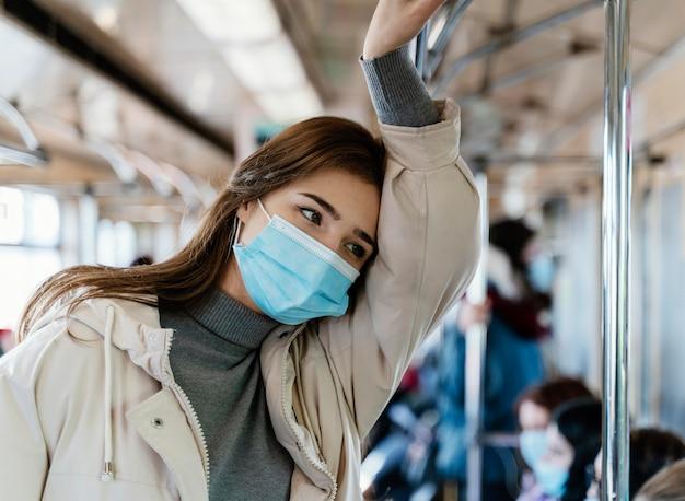 Junge frau, die durch u-bahn reist, die eine chirurgische maske trägt